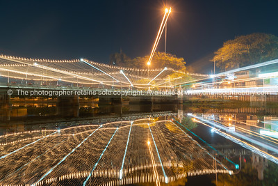 Abstract zoom blur effect of nights lights across Narawat Bridge reflected in Ping River