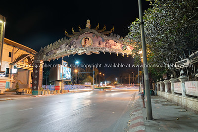 Night street scene of illuminated arch with image of king on raod apprpaching Narawat Bridge.