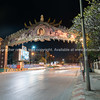 Night street scene of illuminated arch with image of king on raod apprpaching Narawat Bridge.
