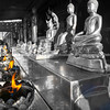 Row of golden Buddha statues on bench with flames burning below in temple grounds of Wat Phra That Doi Suthep