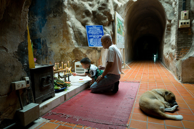 A young boy lights a candle at a shrine in the caves at Wat Umong.
