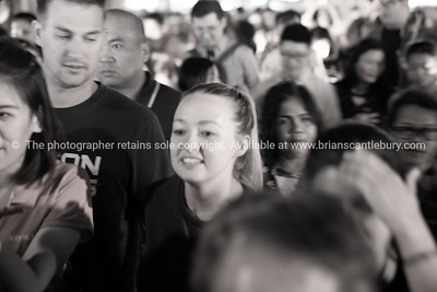 Gritty defocused effect of faces of crowd of people in night street scene illuminated
