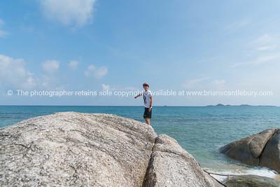 Boy standing on large rock on water's edge on Bang Kao beach Ko Samui.