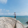 Boy standing on large rock on water's edge on Bang Kao beach Ko Samui.