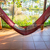 Hammock swings in dark interior of home with view out to luxurious garden and pond.