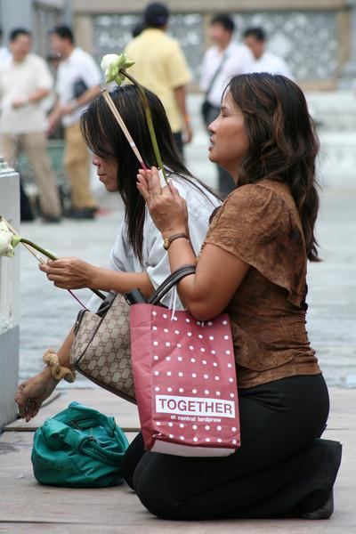 Making merit (with Louis Vuitton handbag); women pray and make offerings at Wat Phra Kaew, Bangkok.