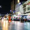 Blurred image of person in orange crossing city street on dark night surrounded by street, shop land vehicle ights with