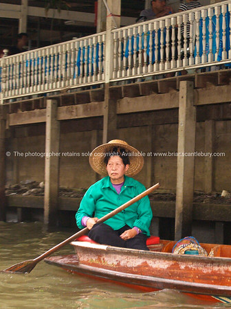 Bangkok life, woman sits looking forelornly in boat on canal. Model released; no, for editorial & personal use.