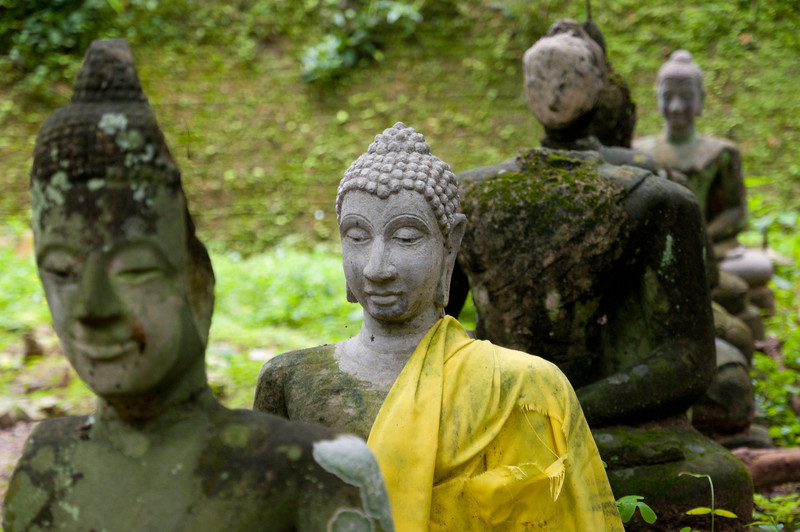 Dozens of crumbling statues of the Buddha sit peacefully outside of the cave complex.