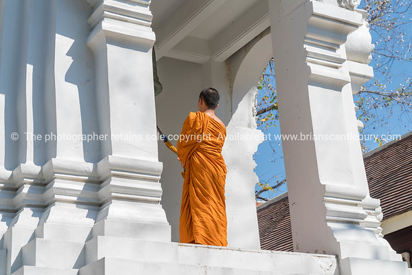 Monk on high level of bell tower ringing bell