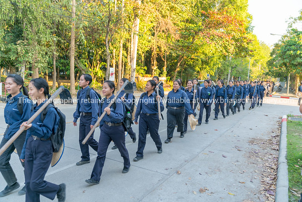Agricultural university students in blue uniform and field hoe over shoulder march to accommodation after days education.