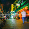 People blurred in motion walk down dark Asian city street towards bright yellow and red massage sign.