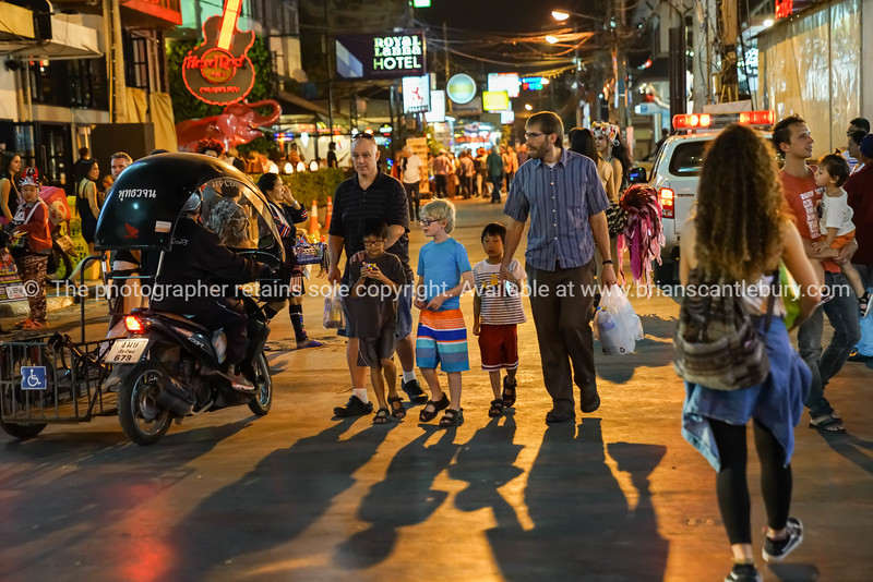 Shadows on street of shopping tourists in busy city at night
