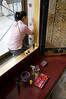 A woman touches up some of the details of Wat Pho, a Bangkok temple featuring an enormous reclining Buddha.