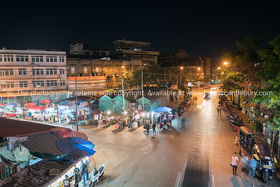 high point of view onto city street markets with people and vehicles blurred in motion