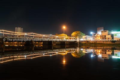 Thailand Bible Society building illuminated across Narawat Bridge and reflected in still water of Ping River at night.