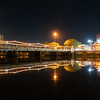 Thailand Bible Society building illuminated across Narawat Bridge and reflected in still water of Ping River at night.