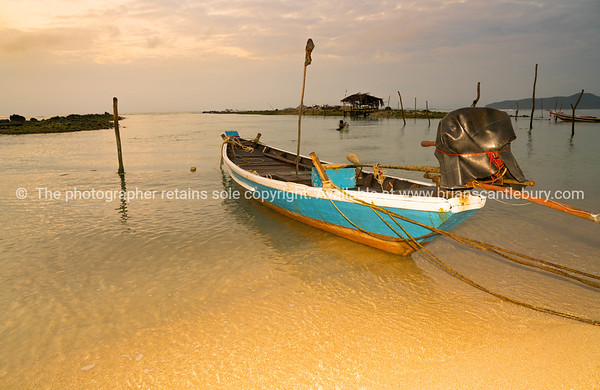 Long tail fisherman's boat moored to beach on seashore