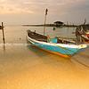 Long tail fisherman's boat moored to beach on seashore
