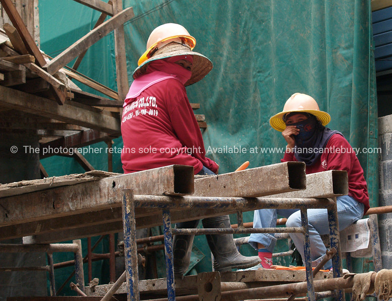 Bangkok life, woman construction workers high on the scaffolding.<br /> Model released; no, for editorial & personal use.