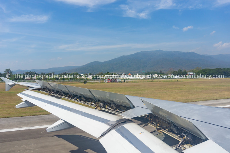 Chiang Mai airport through plane window, runway and planes parked up and waiting