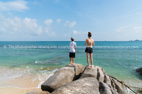 Boy and girl standing in distance on large rock on water's edge on Bang Kao beach Ko Samu