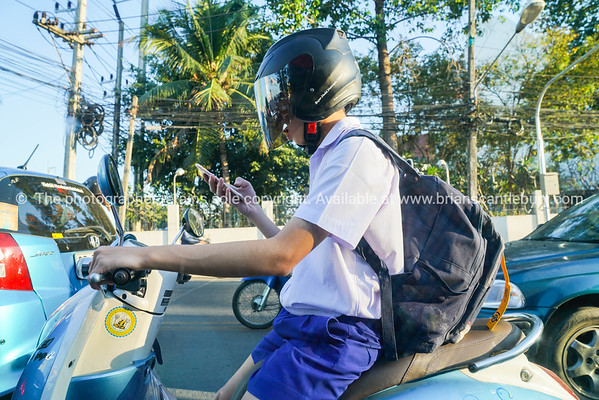 Person on motorcycle using mobile phone