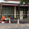Monk in saffron robes sits on corner pavement outside Asian restaurant
