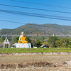 Big grotesque Buddhist monk statue in Thai countryside.