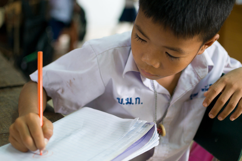A Thai boy draws pictures on a notepad. A school near the elephant park invited we volunteers to the grounds to raise funds. Students played instruments, gave massages, made bracelets, and played in the school yard.