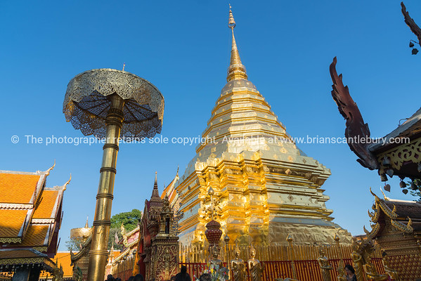 Large golden chedi surrounded by Buddhist architectural structures.