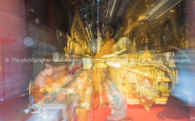 Ethereal image in zoom blur gives mystical effect of Devotee kneel at feet of monk inside temple golden with Buddhist icons.