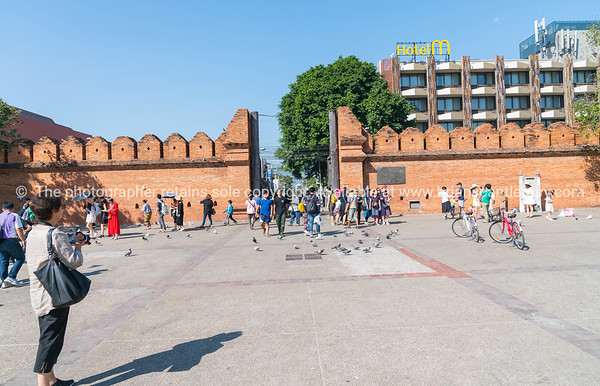 Locals and tourists pass through  Pratu Tha phae Park outside the old city wall east gate.