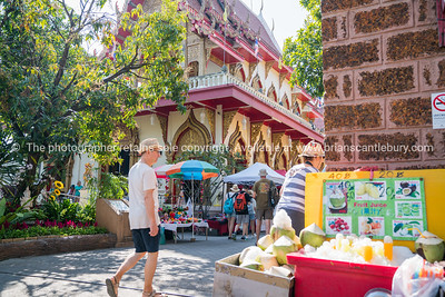people pass coconut stall and Buddhist temple in city street