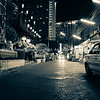 Dark city street illuminated by advertizing and street lights