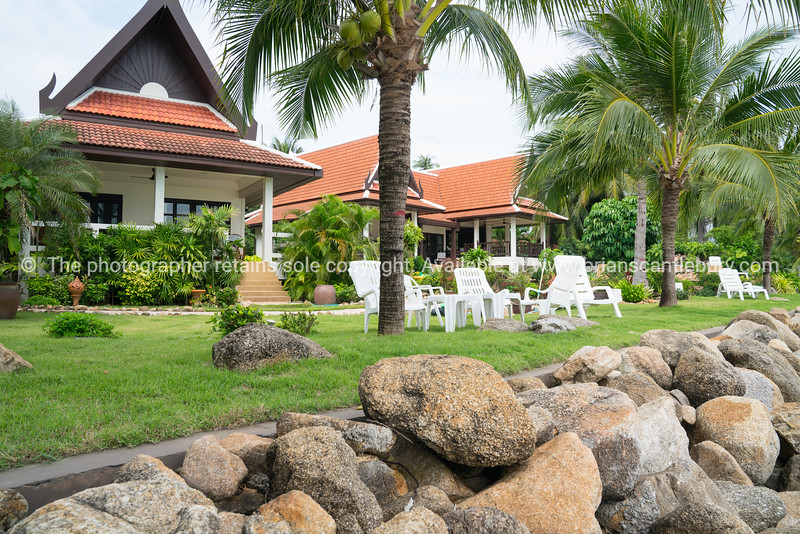 Asian architecturally designed residential properties beyond heavy rock beach wall.