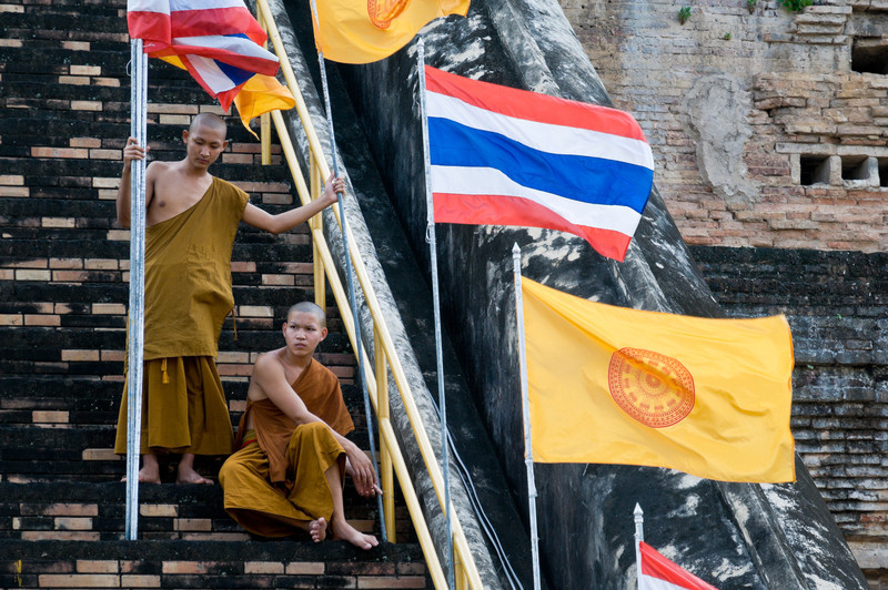 Novice monks remove flags along one of the stairways of Wat Chedi Luang.