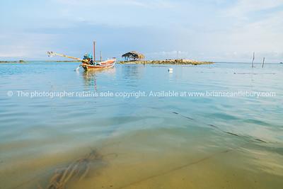 Asian idyllic coastal scene with traditional long tail fishing boats.