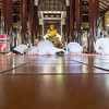 People dressed in all white on Buddhist Temple floor in devotion