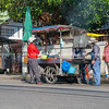 Two people waiting on street for their order of cooked food being prepared by owner of Asian cart parked on side of city road.