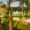 Tropical residential property at night with lights illuminating verandas and landscaped gardens and pond.