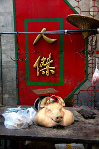 A small market in an alley off a street in Chinatown, Bangkok, Thailand.  The people at the market thought it was funny that we were fascinated with taking so many photo's of the pigs head.