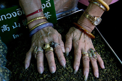 Tea merchant showing off her numerous rings in Chinatown, Bangkok, Thailand.