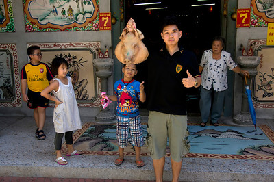 About 40 yards from the little meat market was a small Buddhist temple.  This young man agreed to stand in front of the temple and hold the pigs head to the delight of a group of kids.