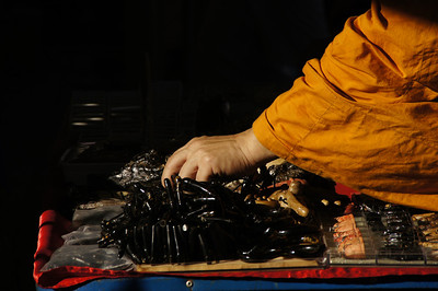 A Buddhist Monk shopping for an Amulet in Chinatown, Bangkok, Thailand.