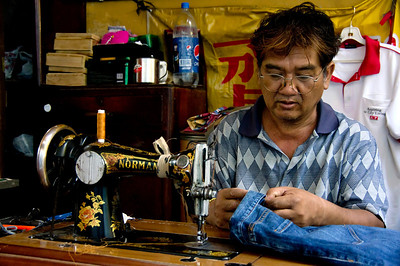 A tailor working with a very old sewing machine on a side street in Chinatown, Bangkok, Thailand.