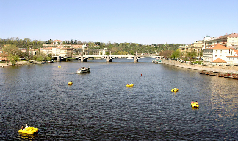 April 14.  On the Charles Bridge over the Vltava River, which was covered with boats, some individual boats like the yellow rafts, and tour boats like the one in the background.  Many other bridges cross the Vltave River in Prague.