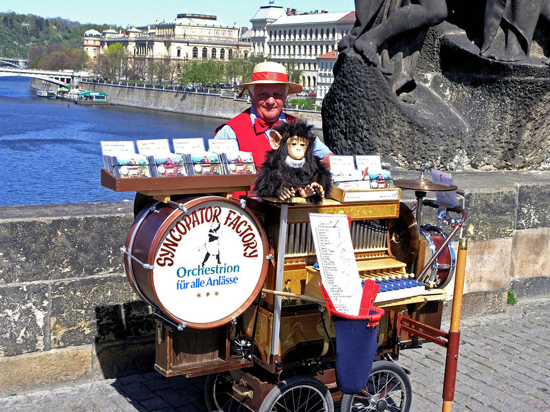 April 14.  The Charles Bridge is crowded with tourists, and musicians, craftsmen, and performers.  Artists of many types will sell you a picture or draw yours quickly.  This organ grinder didn't have a real monkey, but he made this stuffed one do tricks.