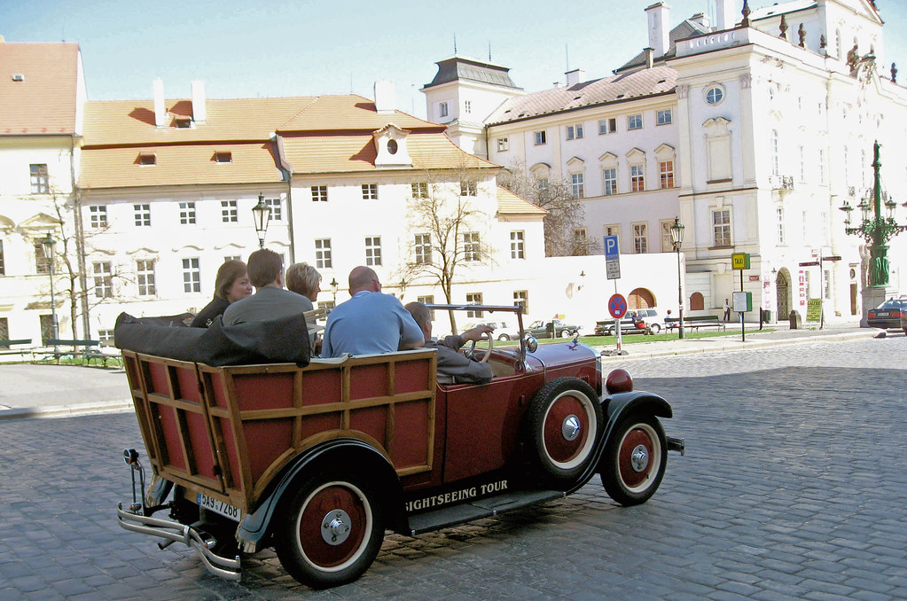 """April 15.  Prague's Castle District is a """"massive complex, including palaces, galleries, churches, and museums,""""  an area where tourists congregate.  In such an area entrepreneurs of all kinds abound.  Would you like to tour the area in an old car?  You can if you want to.  We saw three old cars carrying tourists around."""