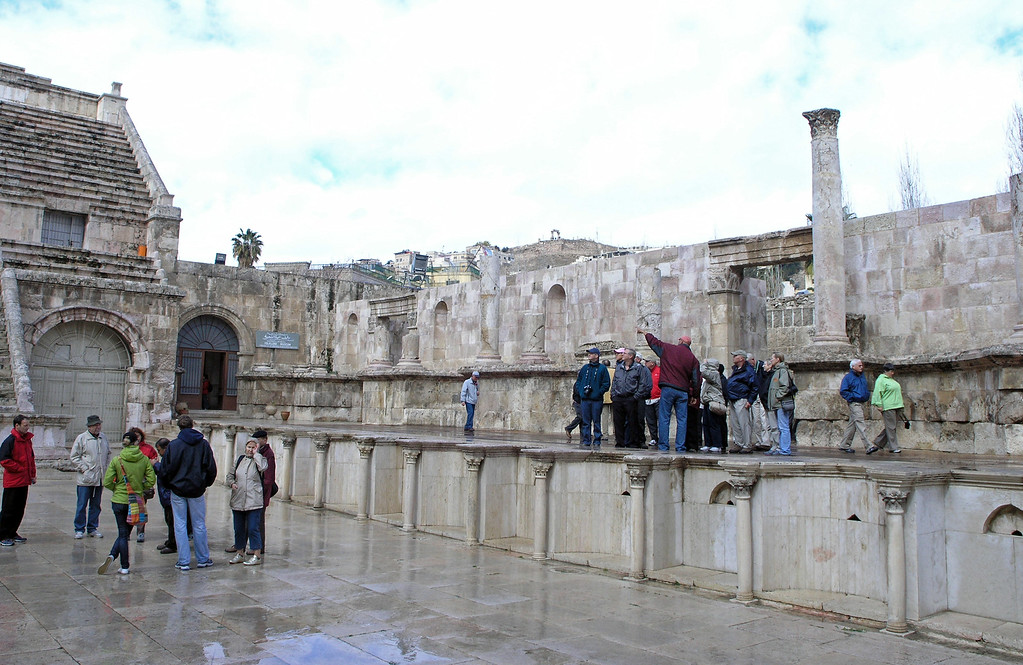 "Feb 17.  This is the amphitheater stage.  Our tour leader, Iyad (pronounced ""Ian""), is pointing out something to our group.  Betty is beside Iyad and is wearing her OAT raincoat and is carrying her big purse.  The blue sign to the left indicates the Folklore Museum.  Later we toured that and the other museum.  The amphitheater was glistening from the little rain that fell this morning, and as you can tell by the coats, it was chilly."